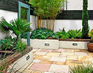 Dublin garden design of a small courtyard with sandstone paving and mirror.