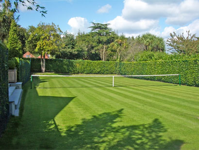 A tennis court was built in the country garden to meet the family's needs.